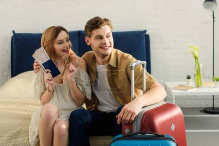 young cheerful couple with travel bags sitting on bed and holding tickets with passports