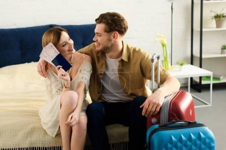 Photo pour Couple souriant avec valises sur le lit et tenant des billets avec passeports - image libre de droit
