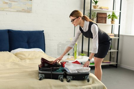 Photo for Businesswoman packing suitcase for business trip - Royalty Free Image
