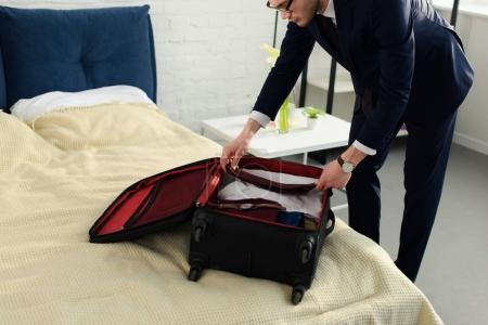 Photo pour Bel homme d'affaires professionnel en costume d'emballage des bagages pour voyage d'affaires - image libre de droit