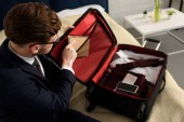 handsome businessman packing diary, smartphone and clothes in travel bag