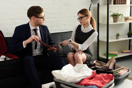 professional couple packing suitcase for business trip together