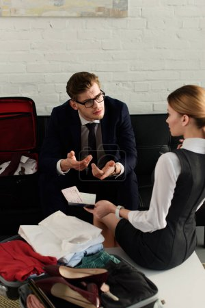 business couple discussing business trip while packing travel bag