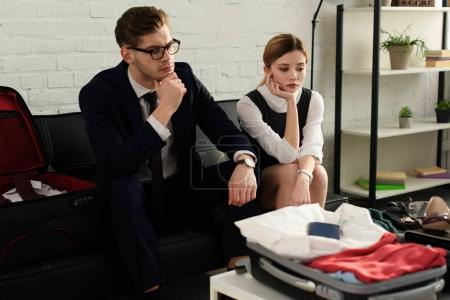 upset businesswoman and businessman couple looking on travel bag for business trip