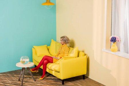 femme en vêtements rétro lumineux, reposant sur le sofa à Appartement coloré, concept de maison de poupée