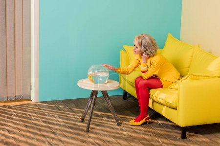 woman in bright retro clothing looking at aquarium fish while resting on sofa at colorful apartment, doll house concept