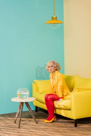 woman in bright retro clothing resting on sofa at colorful apartment, doll house concept
