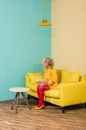 woman in bright retro clothing with golden fish in aquarium resting on sofa at colorful apartment, doll house concept
