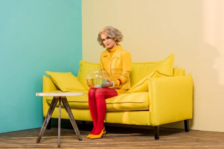 woman in bright retro clothing with golden fish in aquarium on sofa at colorful apartment, doll house concept