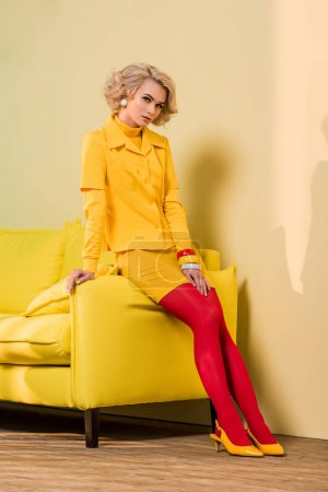 thoughtful young woman in retro clothing sitting on yellow sofa, doll house concept
