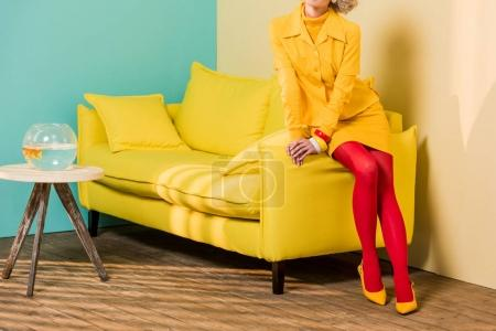 cropped shot of woman in retro clothing on sofa at colorful apartment, doll house concept