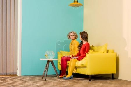 retro styled women sitting on yellow sofa with aquarium fish on coffee table at colorful apartment, doll house concept
