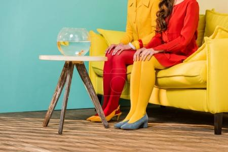 partial view of retro styled women sitting on yellow sofa with aquarium fish on coffee table at colorful apartment, doll house concept