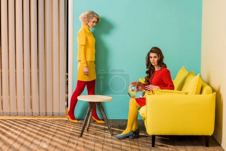 young retro styled women in colorful apartment with yellow sofa and aquarium fish, doll house concept