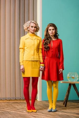 women in bright retro styled clothing holding hands at colorful apartment, doll house concept