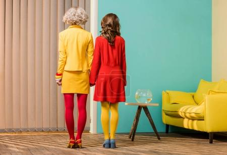 back view of women in bright retro styled clothing holding hands at colorful apartment, doll house concept