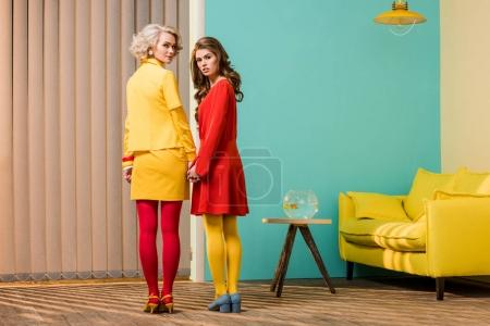 rear view of women in bright retro styled clothing holding hands at colorful apartment, doll house concept
