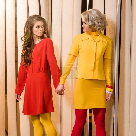 women in bright retro styled clothing holding hands and looking at each other, doll house concept