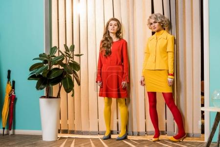young retro styled women standing at window in bright room, doll house concept