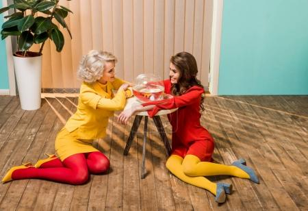 smiling retro styled women sitting on floor near golden fish in aquarium on coffee table, doll house concept