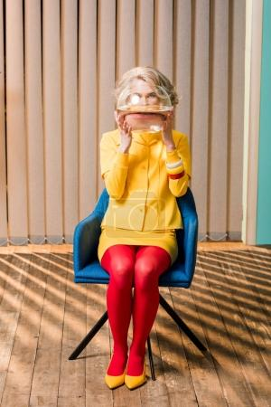 obscured view of woman in retro clothing holding golden fish in aquarium at colorful apartment, doll house concept