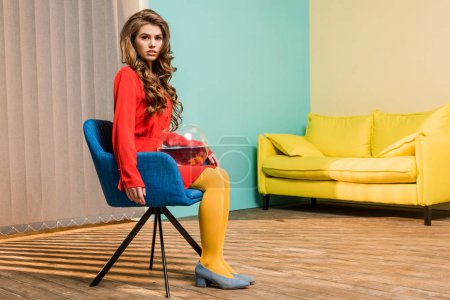 Photo for Young woman in retro clothing with golden fish in aquarium sitting on chair at colorful apartment, doll house concept - Royalty Free Image