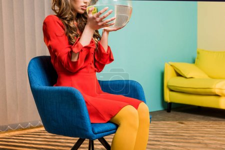 partial view of woman in retro clothing with golden fish in aquarium sitting on chair at colorful apartment, doll house concept