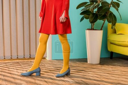 cropped shot of woman in bright clothing standing at colorful room, doll house concept