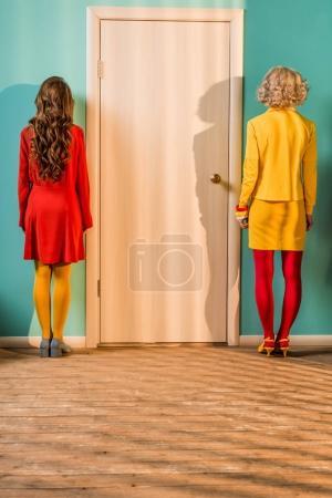 Photo pour Vue arrière du rétro style femmes se tenant debout à la porte de l'appartement coloré, concept de maison de poupée - image libre de droit
