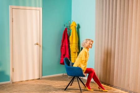 side view of pensive retro styled woman sitting on chair at bright apartment, doll house concept