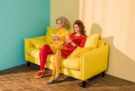 rétro style utilisatrices des smartphones tout en reposant sur le canapé jaune, concept de maison de poupée