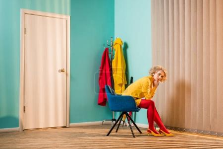 Photo for Side view of retro styled woman sitting on chair at bright apartment, doll house concept - Royalty Free Image