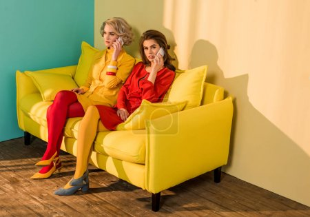 retro styled women talking on smartphones on yellow sofa, doll house concept