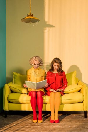 women in retro clothing reading books sitting on yellow sofa at bright apartment, doll house concept