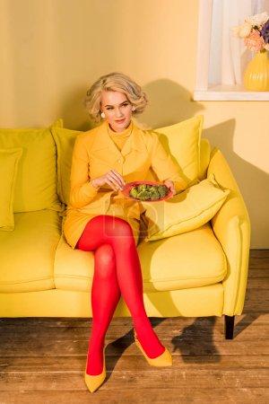 rétro style femme avec brocoli sur plaque reposant sur le sofa à appartement lumineux, concept de maison de poupée