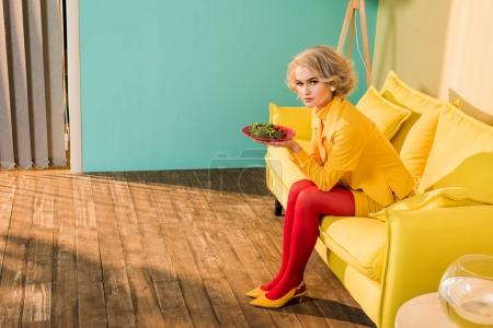 retro styled woman with broccoli on plate resting on sofa at bright apartment, doll house concept