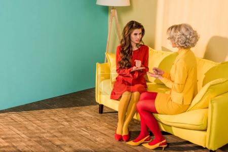 retro styled beautiful girls in colorful dresses playing rock paper scissors game at home