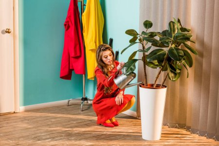 beautiful woman in red dress squatting and watering plant with watering can at home