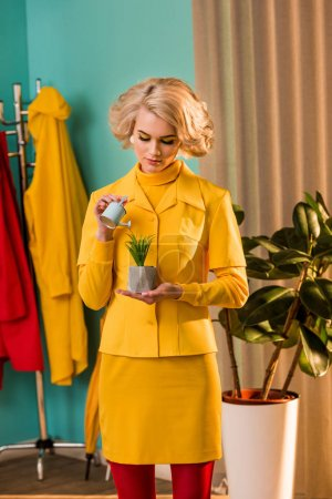 beautiful old-fashioned woman in yellow dress watering potted plant with small watering can at home