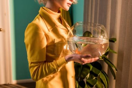 cropped image of stylish woman holding aquarium with gold fish at home