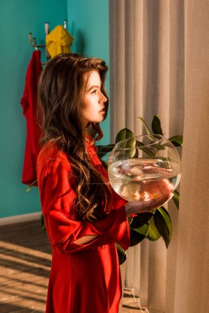 side view of stylish woman in red dress holding aquarium with gold fish and looking away at home