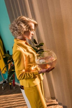side view of beautiful stylish woman holding aquarium with gold fish at home