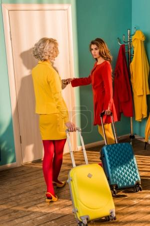 Beautiful old-fashioned girls in colorful dresses with travel bags walking to door at home