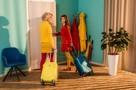 Photo for Beautiful retro styled girls in colorful dresses with travel bags walking to door at home - Royalty Free Image