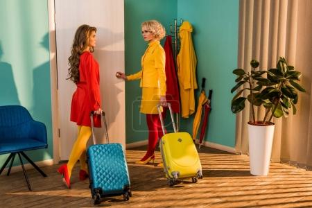 beautiful old-fashioned girls in colorful dresses with travel bags opening door at home