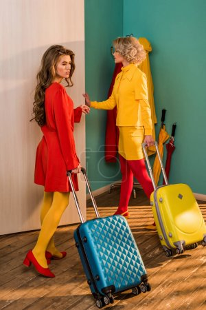 beautiful retro styled girls in colorful dresses with travel bags opening door at home