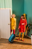 beautiful retro styled girls in colorful dresses entering room with travel bag at home