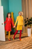 beautiful old-fashioned girls in colorful dresses entering apartment and holding hands at home