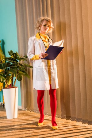 beautiful retro styled doctor in colorful dress reading diagnosis in clipboard in clinic
