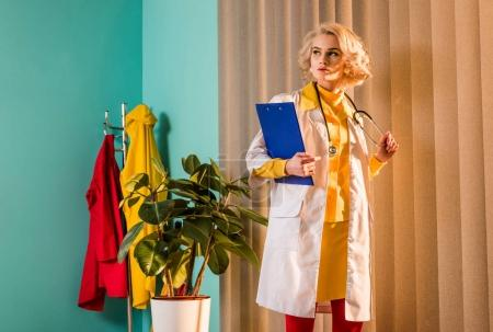beautiful retro styled doctor in colorful dress holding clipboard and stethoscope in clinic